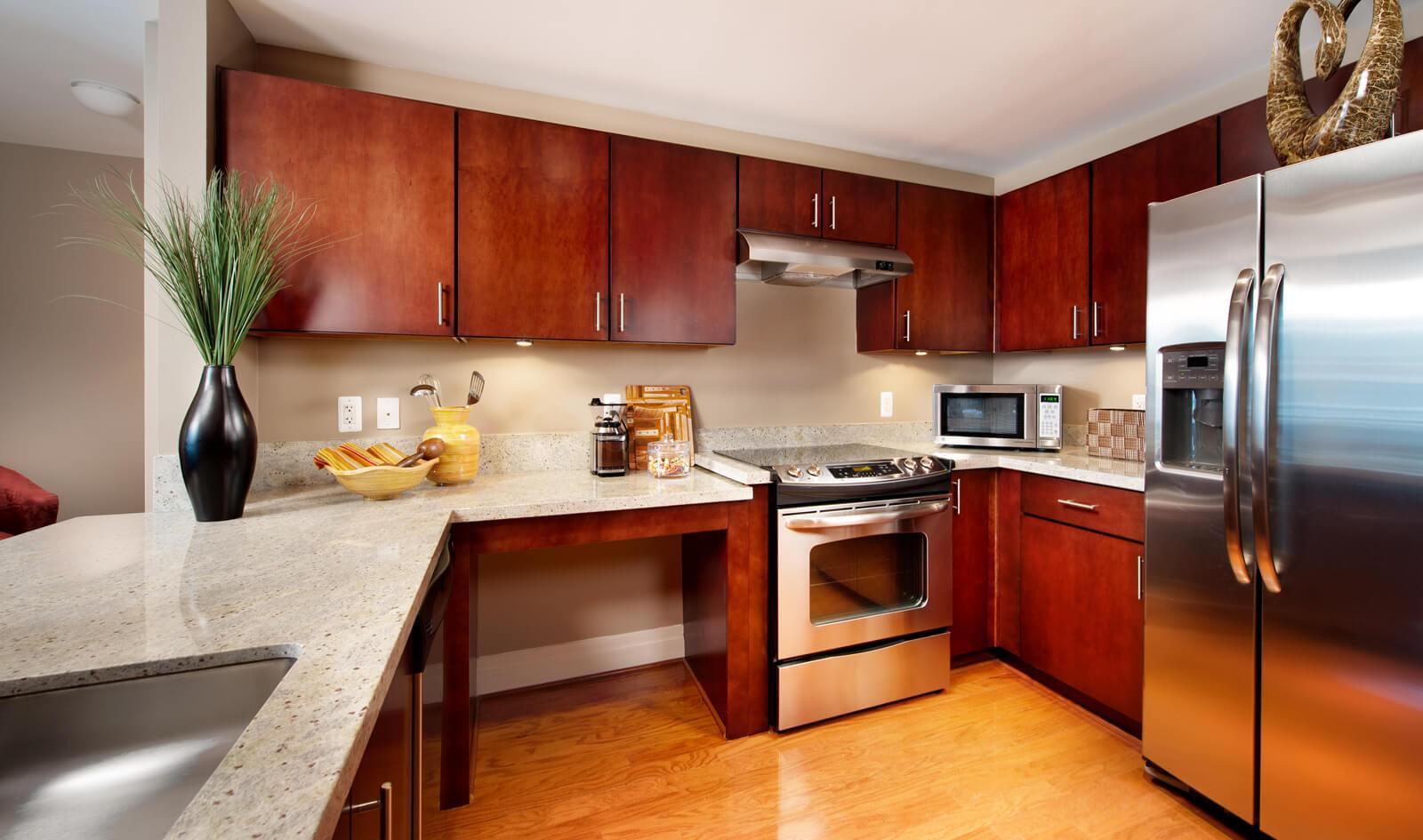 slide image Enjoy Kashmire white granite countertops, Merillat Sedona cabinetry and GE Stainless Steel appliances.